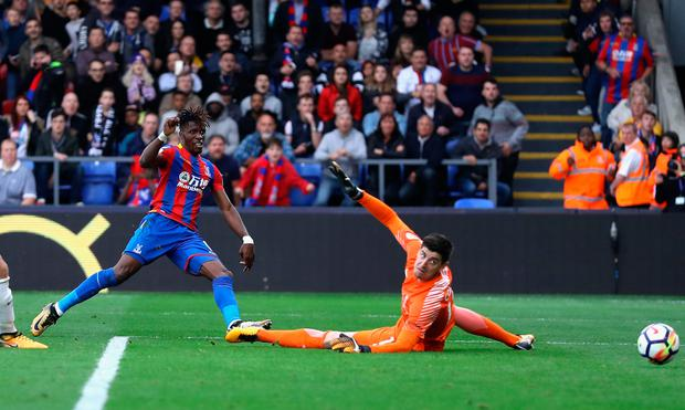 Wilfried Zaha of Crystal Palace scores his sides second goal past Thibaut Courtois of Chelsea. Photo: Getty Images