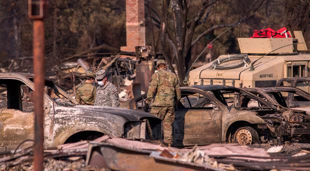Troops from three California National Guard companies search through a fire-devastated neighborhood on October 14, 2017 in Santa Rosa, California. (Photo by David McNew/Getty Images)