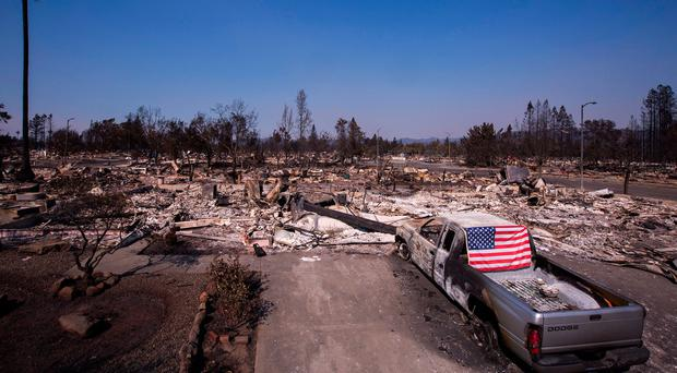 A flag is draped on a burned truck in the fire-devastated Coffey Park neighborhood, Santa Rosa, California. (Photo by David McNew/Getty Images)