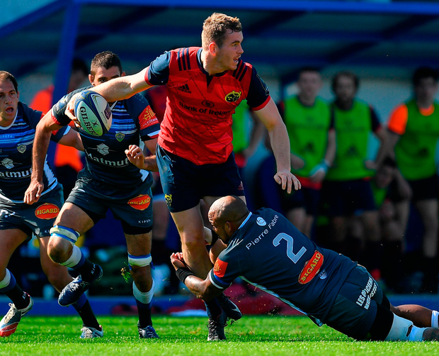 Munster's Chris Farrell gets the ball way as he is tackled by Jody Jenneker of Castres. Photo: Brendan Moran/Sportsfile