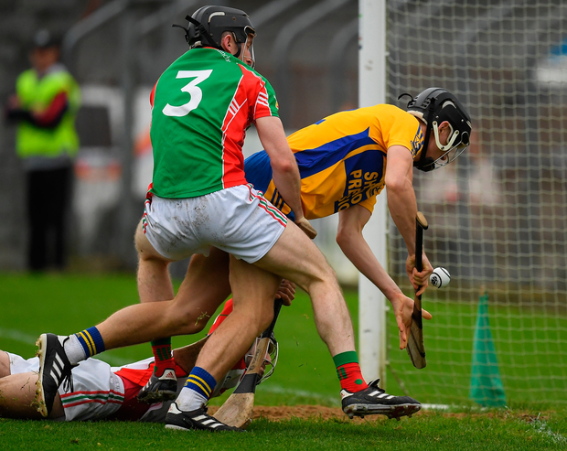 Shane Golden of Sixmilebridge is fouled by Clooney Quin goalkeeper Keith Hogan and full-back Shane McNamara before scoring a goal in the Clare SHC final at Cusack Park. Photo: Sportsfile