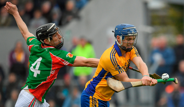 Sixmilebridge's Brian Corry keeps possession from Clooney Quin's Ruaidhrí McNamara. Photo: Sportsfile
