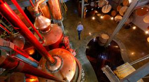 A woman walks beneath copper brandy stills at the KWV distillery in Paarl near Cape Town, South Africa. Photo: Reuters