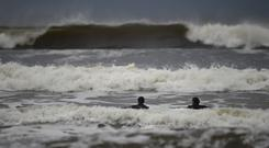 Surfers watch as waves approach in the Atlantic on the eve of storm Ophelia in an area where the tide should be out in the County Clare town of Lahinch, Ireland October 15, 2017. REUTERS/Clodagh Kilcoyne