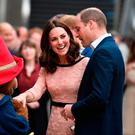 Britain's Catherine, Duchess of Cambridge, (C) laughs as she shakes hands with a person in a Paddington Bear outfit along with her husband Britain's Prince William, Duke of Cambridge, (R) as they attend a charities forum event at Paddington train station in London on October 16, 2017