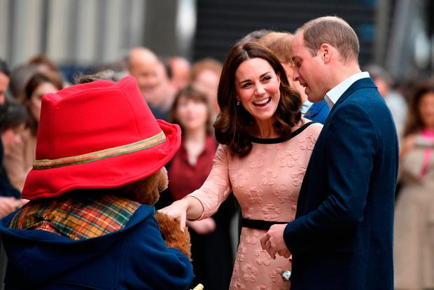 Britain's Catherine Duchess of Cambridge  laughs as she shakes hands with a person in a Paddington Bear outfit along with her husband Britain's Prince William Duke of Cambridge  as they attend a charities forum event at Paddington train station