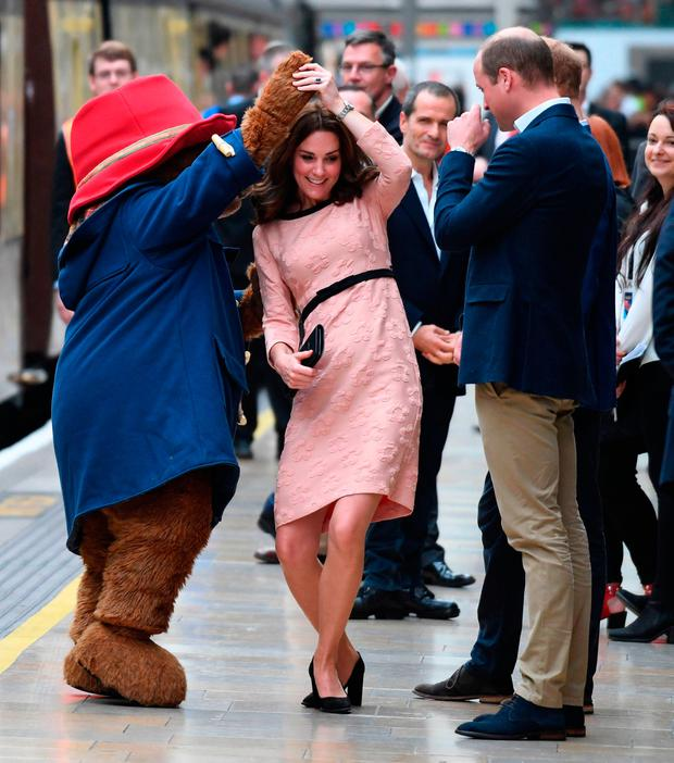 Britain's Catherine, Duchess of Cambridge, (C) dances with a person in a Paddington Bear outfit by her husband Britain's Prince William, Duke of Cambridge as they attend a charities forum event at Paddington train station in London on October 16, 2017