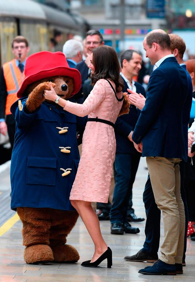 Britain's Catherine, Duchess of Cambridge, (C) dances with a person in a Paddington Bear outfit by her husband Britain's Prince William, Duke of Cambridge, (R) as they attend a charities forum event at Paddington train station in London on October 16, 2017