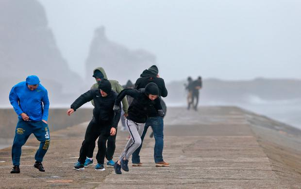 People brave the winds and rain on Howth Pier pictured this afternoon at the height of Hurricane Ophelia Picture Colin Keegan, Collins Dublin.