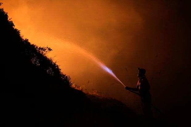 A volunteers uses a water hose to fight a wild fire raging near houses in the outskirts of Obidos, Portugal, in the early hours of Monday, Oct. 16 2017. (AP Photo/Armando Franca)