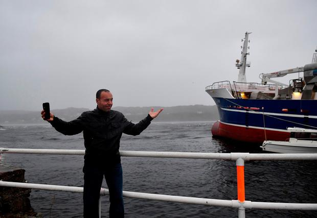 DONEGAL, IRELAND - OCTOBER 16: A man takes a selfie with his smartphone during Hurricane Ophelia at Killybegs harbour on October 16, 2017 in Donegal, Ireland. The hurricane hit the north west coast of Ireland early this afternoon with winds in excess of 80mph. The Irish government have issued a red weather warning whilst amber weather warnings remain in place for Northern Ireland and parts of Wales. (Photo by Charles McQuillan/Getty Images)