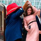 The Duchess of Cambridge dances with a costumed figure of Paddington bear on platform 1 at Paddington Station, London, as she attends the Charities Forum event. Photo: PA