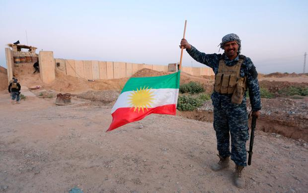 An Iraqi soldier holds the Kurdish flag upside down after his army seized enemy positions in Kirkuk. Photo: REUTERS/Stringer