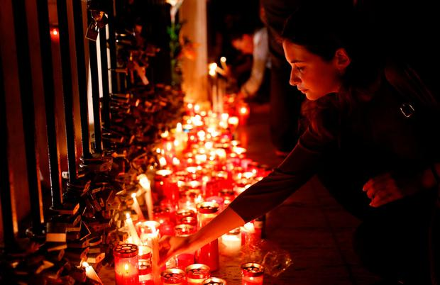 A woman places a candle on the Love monument during a silent candlelight vigil to protest against the assassination of investigative journalist Daphne Caruana Galizia in a car bomb attack, in St Julian's, Malta, October 16, 2017.