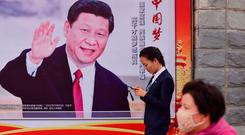 Above: People walk past a poster featuring Chinese President Xi Jinping with a slogan reading 'Chinese Dream, People's Dream' on a roadside in Beijing. Picture: AFP