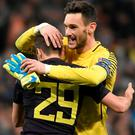 Tottenham Hotspur's French goalkeeper Hugo Lloris (R) and Tottenham Hotspur's English midfielder Harry Winks celebrate after the UEFA Champions League group H football match Real Madrid CF vs Tottenham Hotspur FC at the Santiago Bernabeu stadium in Madrid