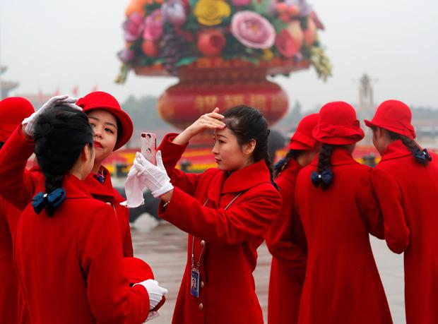 Ushers prepare themselves for photos at Tiananmen Square. Photo: Reuters/Ahmad Masood