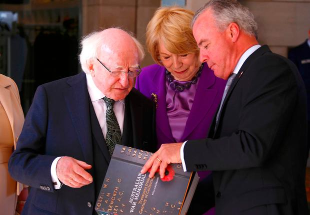 Irish President Michael Higgins, left, and his wife Sabina are presented with a book from Director of the Australian War Memorial Brendan Nelson during an official visit to the Australian War Memorial in Canberra, Monday, Oct. 16, 2017. (David Gray/Pool Photo via AP)