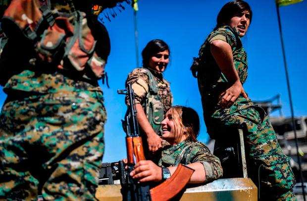 Kurdish female fighters of the Syrian Democratic Forces celebrate in Raqa after retaking the city from Isil fighters. Photo: Getty Images