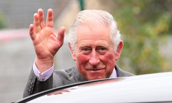 The Prince of Wales waves to well-wishers outside the Eglinton Community Centre in Londonderry during a visit to communities hit by the summer's flash floods. Photo: Laura Hutton/PA Wire