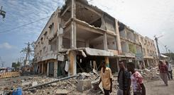 Men walk near destroyed buildings as thousands of Somalis gathered to pray at the site of the country's deadliest attack and to mourn the hundreds of victims, at the site of the attack in Mogadishu, Somalia Friday, Oct. 20, 2017. More than 300 people were killed and nearly 400 wounded in Saturday's truck bombing, with scores missing. (AP Photo/Farah Abdi Warsameh)