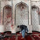 An Afghan man inspects inside a damaged mosque in Kabul, Afghanistan, Saturday, Oct. 21, 2017, a day after a suicide attack.