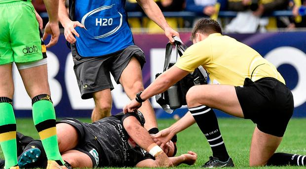 The referee (R) tends to Clermont's French scrum-half Morgan Parra (Bottom) suffering from concussion during the European Rugby Champions Cup match ASM Clermont Auvergne vs Northampton Saints at the Marcel-Michelin stadium