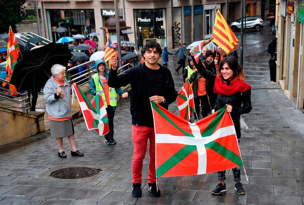 People hold Catalan pro-independence Estelada flags and Basque Country flags during a demonstration in the northern Spain Basque village of Beasain yesterday to support the movement led by Carles Puigdemont. Photo: GETTY