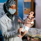 A Syrian infant suffering from severe malnutrition is carried by a nurse at a clinic in the rebel-controlled town of Hamouria, in the eastern Ghouta region on the outskirts of the capital Damascus, on October 21, 2017