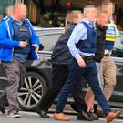 A man (second from the right, black jumper) was arrested by gardai at CityWest Shopping Centre this afternoon