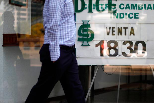 A man walks in front of a board displaying the exchange rate for Mexican peso and US dollars at a foreign exchange house in Mexico City