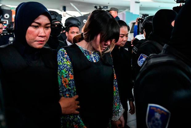 Vietnamese defendant Doan Thi Huong (C) is escorted by police personnel towards the low-cost carrier Kuala Lumpur International Airport 2 (KLIA2) in Sepang during a visit to the scene of the murder as part of the Shah Alam High Court trial process on October 24, 2017, for her alleged role in the assassination of Kim Jong-Nam.