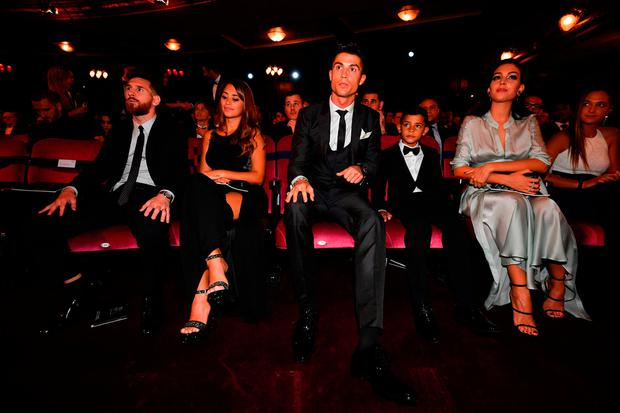 Nominees for the Best FIFA football player, Barcelona and Argentina forward Lionel Messi (L) with his wife Antonella Roccuzzo (2nd L) take their seats next to Real Madrid and Portugal forward Cristiano Ronaldo (C), his son Cristiano Ronaldo Jr (2nd R) and his partner Georgina Rodriguez, for The Best FIFA Football Awards ceremony, on October 23, 2017 in London. / AFP PHOTO / Ben STANSALLBEN STANSALL/AFP/Getty Images