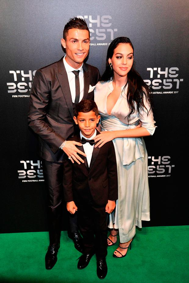 Real Madrid and Portugal forward Cristiano Ronaldo (L) poses for a photograph with partner Georgina Rodriguez (R) and his son Cristiano Ronaldo Jr as he arrives for The Best FIFA Football Awards ceremony, on October 23, 2017 in London. / AFP PHOTO / Glyn KIRKGLYN KIRK/AFP/Getty Images