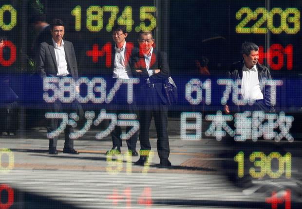 Passersby are reflected in an electronic stock quotation board outside a brokerage in Tokyo, Japan. Photo: Reuters