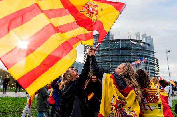 Women hold Spanish and Catalan flags during a demonstration against Catalonia's independence in front of the European Parliament in Strasbourg. Photo: Getty Images