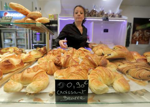 An employee places all-butter croissants for sale at the bakery