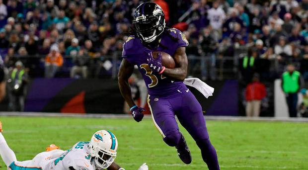 Baltimore Ravens running back Alex Collins (34) runs past Miami Dolphins safety Michael Thomas (31) during the second quarter at M&T Bank Stadium. Credit: Tommy Gilligan-USA TODAY Sports