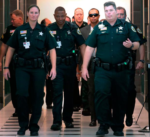 Tiger Woods, center right, makes his way into a North County Courthouse courtroom in Palm Beach Gardens