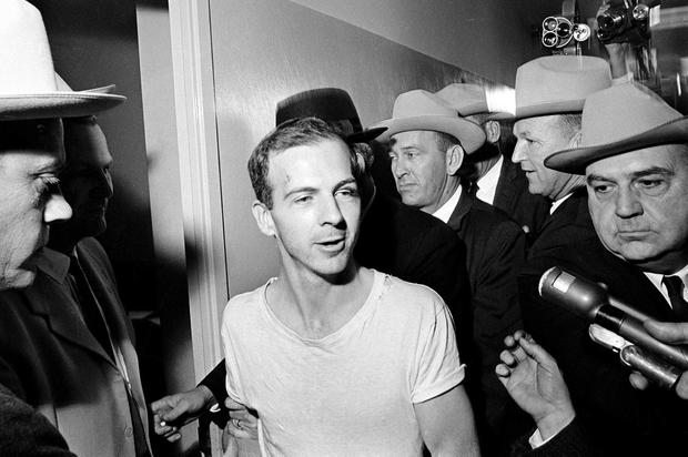 Lee Harvey Oswald talks to the media as he is led down a corridor of the Dallas police station for another round of questioning.