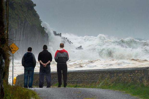 The now famous image of three men in mourning as waves crash against the coastline in Ballinskelligs, Co Kerry Photo: Stephen Kelleghan