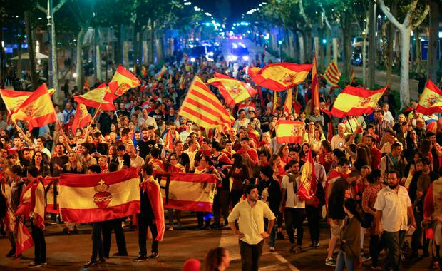 Pro unity demonstrators wave Spanish and Catalan flags during a protest after the Catalan regional parliament declared independence from Spain