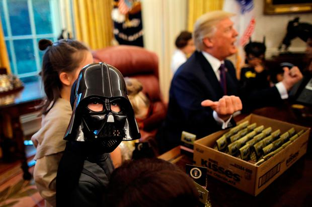 U.S. President Donald Trump gives out Halloween treats to children of members of press and White House staff in the Oval Office of the White House in Washington, U.S., October 27, 2017. REUTERS/Carlos Barria