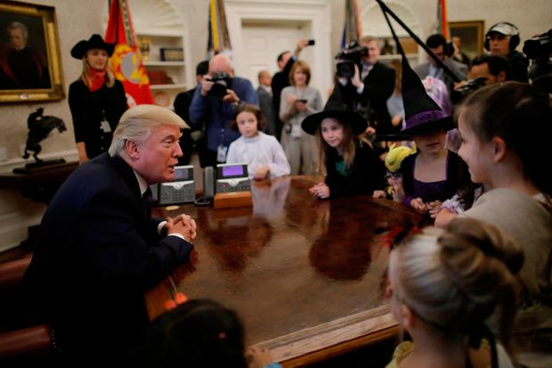 U.S. President Donald Trump meets with children of members of press and White House staff as he gives out Halloween treats in the Oval Office of the White House in Washington, U.S., October 27, 2017. REUTERS/Carlos Barria