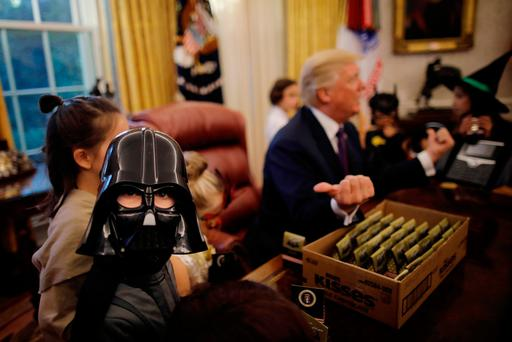 U.S. President Donald Trump gives out Halloween treats to children of members of press and White House staff in the Oval Office of the White House in Washington, DC, U.S. October 27, 2017. REUTERS/Carlos Barria