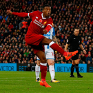 Georginio Wijnaldum fires Liverpool's third and final goal past a cluster of Huddersfield defenders at Anfield yesterday. Photo: Phil Noble/Reuters