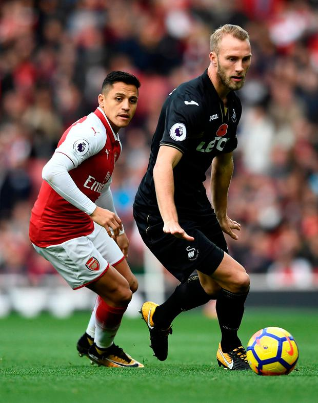Arsenal's Alexis Sanchez in action with Swansea City's Mike van der Hoorn. Photo: Dylan Martinez/Reuters