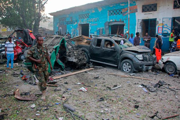 Somali soldier walk near wreckage of vehicles after a car bomb was detonated in Mogadishu, Somalia Saturday, Oct 28, 2017. AP Photo/Farah Abdi Warsameh)