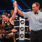 Referee Steve Gray raises Katie Taylor's hand in victory as she celebrates winning the WBA World Lightweight Title with mother Bridget Taylor. Photo: Sportsfile