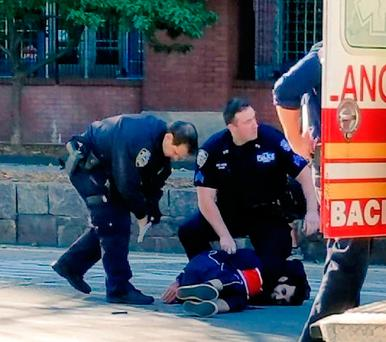 Tthe suspect lies on the ground surrounded by police officers. Photo: NBC